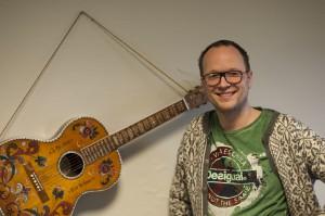 Gunnar Sigve poserar ved bestefaren sin gitar